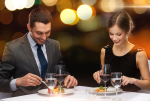restaurant, couple and holiday concept - smiling couple eating m